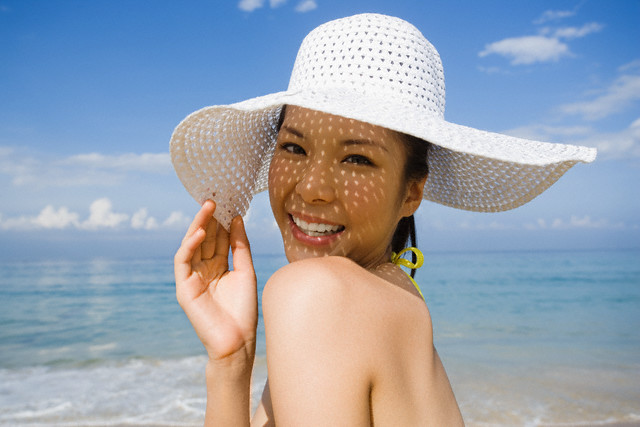 Phuket, Thailand --- Woman Wearing a Bikini and Straw Hat --- Image by © Ken Seet/Corbis